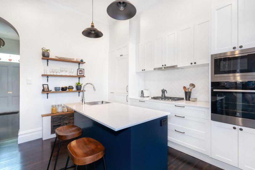 Apartment renovation in Balmain, Sydney with white shaker cabinet doors, white herringbone splashback and blue feature cabinetry in the island