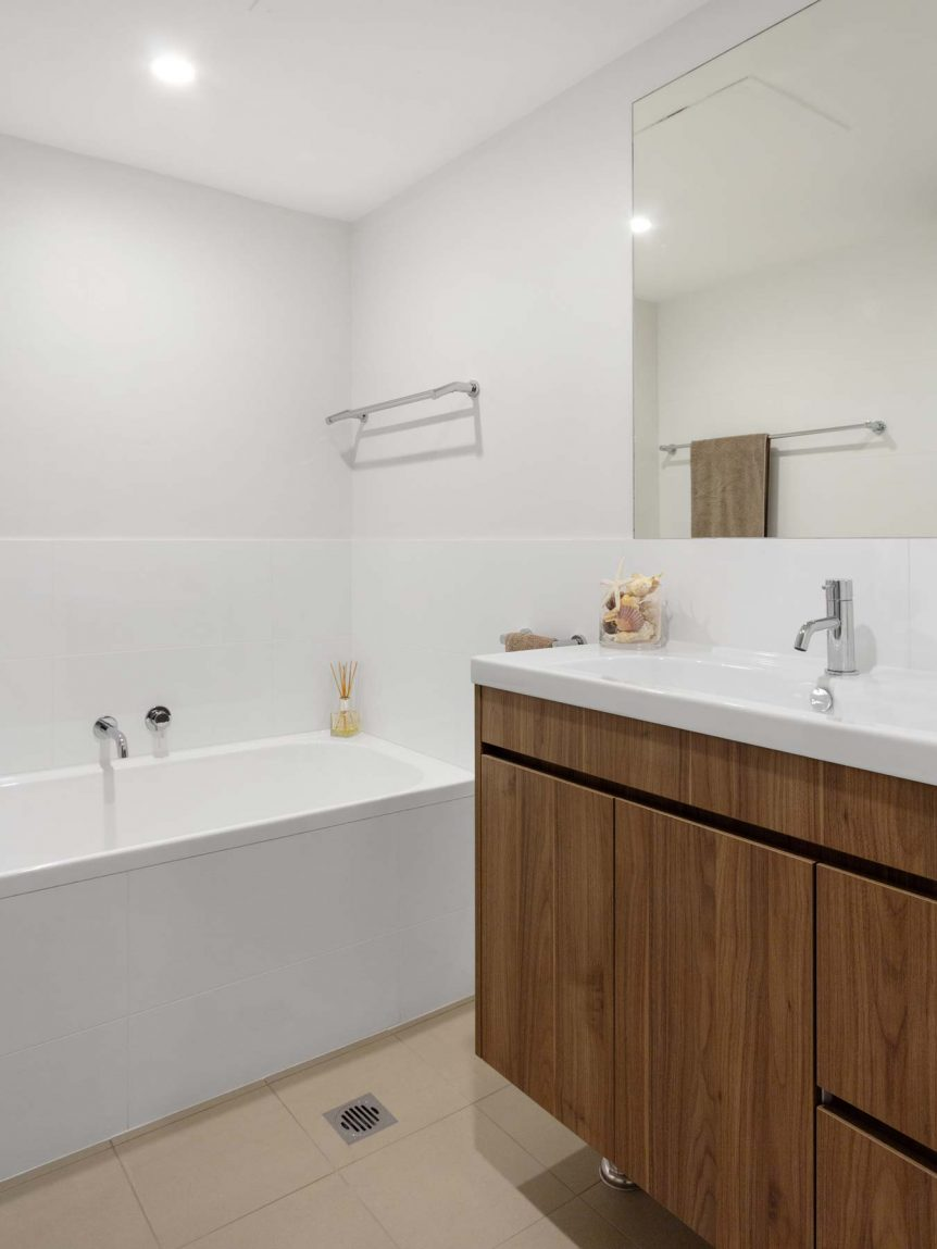 Bathroom renovation Sydney featuring custom made timber look vanity in Walnut.