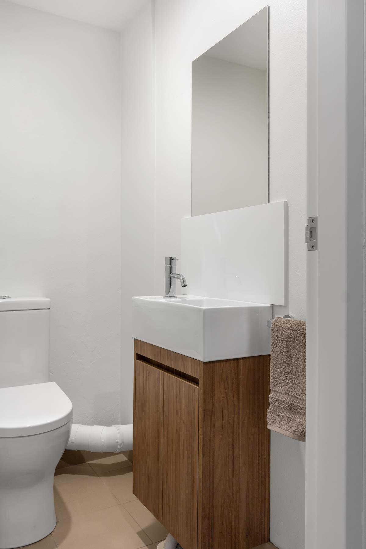 Bathroom renovation Sydney featuring custom made timber look vanity in Walnut.