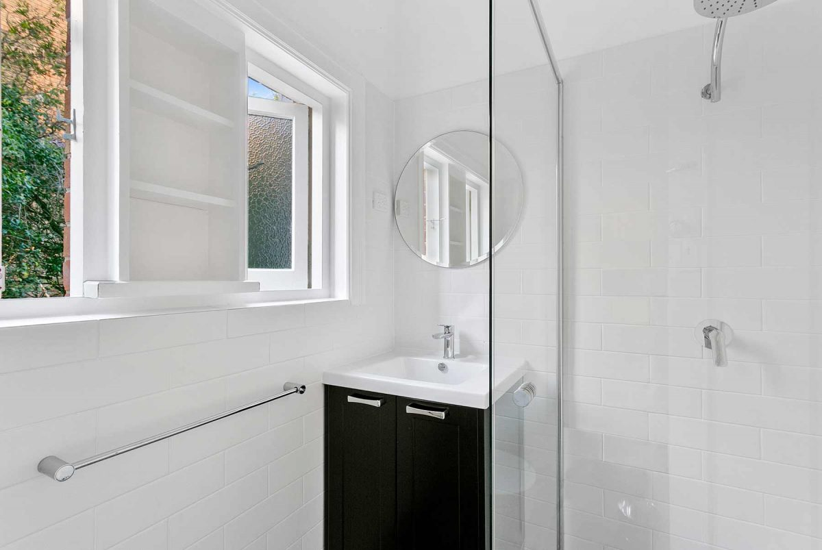 Bathroom with custom made compact vanity and round mirror. Apartment renovation in Fairlight, by Reno Pack Sydney.