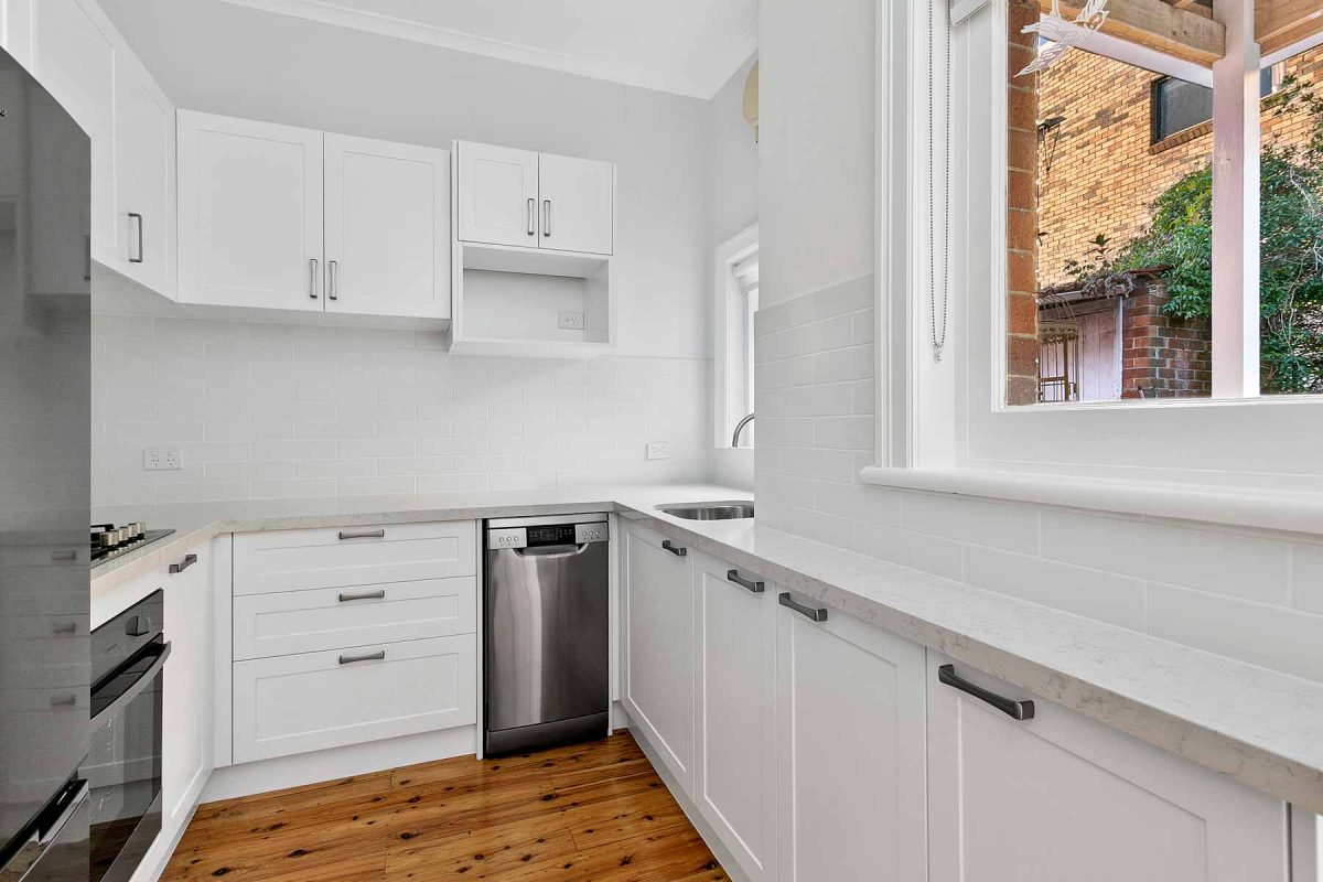 Apartment renovation in Fairlight, Sydney. New kitchen with white shaker cabinets and subway tiled splashback.