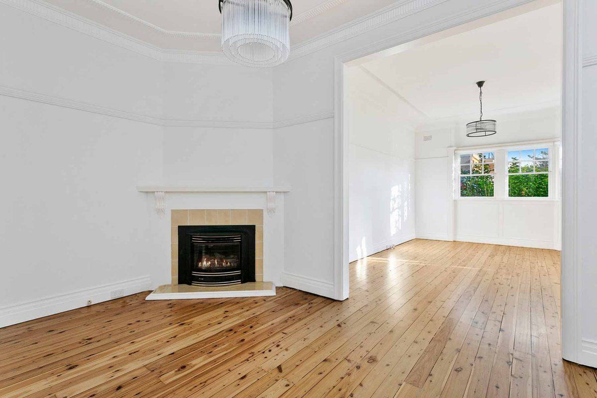 Apartment renovation in Fairlight, Sydney with polished timber floors and fireplace
