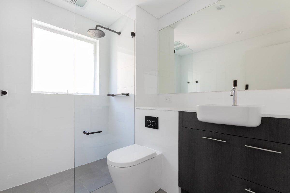 Apartment bathroom renovation in Summer Hill featuring Laminex custom vanity, Caroma basin, black Phoenix tapware & Paco Jaanson toilet