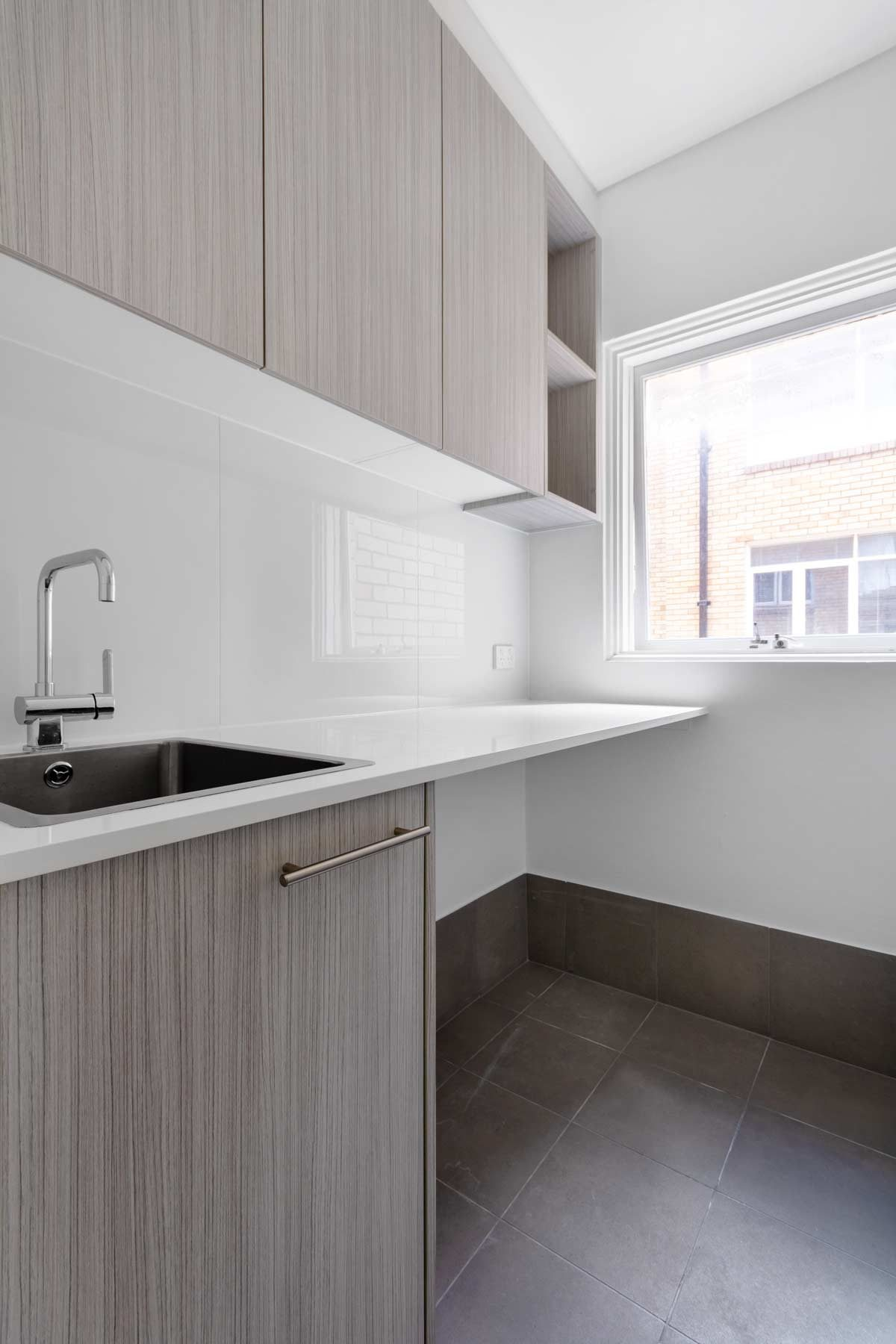 Apartment laundry renovation in Summer Hill featuring Laminex cabinetry, Caroma tapware and Abey sink.